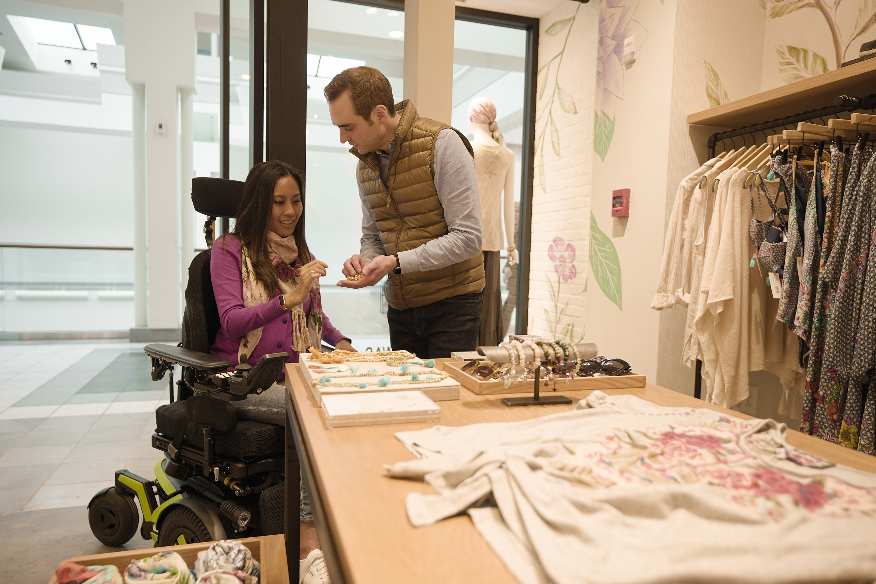 An Asian woman using a Corpus F3 power chair shops for jewelry with a Caucasian man. She is wearing a pink sweater and jeans. She smiles while the man holds some jewelry for her to look at. The man wears a gold puffer vest and black jeans.