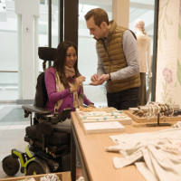 An Asian woman using a Corpus F3 power chair shops for jewelry with a Caucasian man. She is wearing a pink sweater and jeans. She smiles while the man holds some jewelry for her to look at. The man wears a gold puffer vest and black jeans. thumbnail