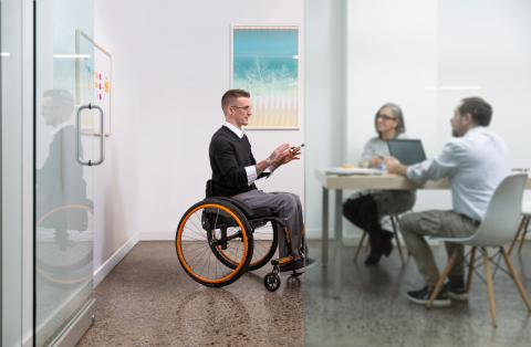 A person in an Apex wheelchair with orange detailing meets with two others at a table. They are gesturing with their hands and the other two people are listing intently.