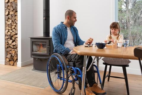 A man using a Helio C2 wheelchair sits at a table with his daughter, eating breakfast. There is a wood burning stove and a stack of chopped firewood in the background.