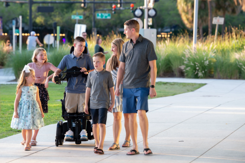 A young person in a standing power chair wheels along a path with their family.